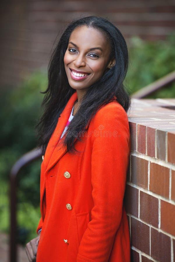 站立年轻非裔美国人的微笑的女商人户外 免版税库存图片