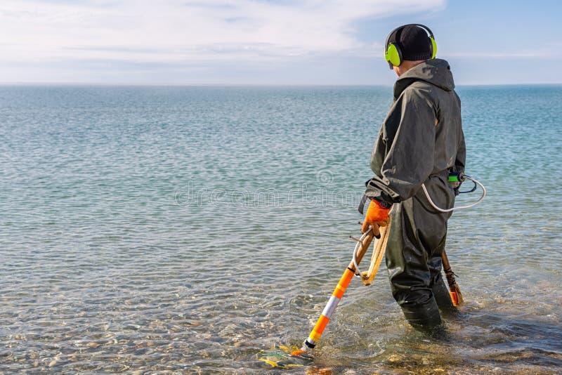 站立knee-deep在水中的一个人寻找与金属探测器的贵重金属 海和天空在背景 历史 免版税库存照片