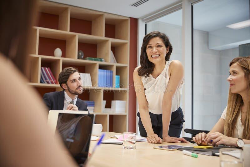 站起来在会议室会议,关闭上的女性经理 免版税图库摄影