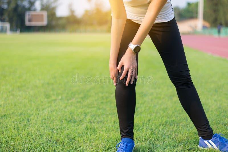 竞技妇女赛跑者手接触和有膝盖痛苦和伤害在跑以后室外 免版税图库摄影