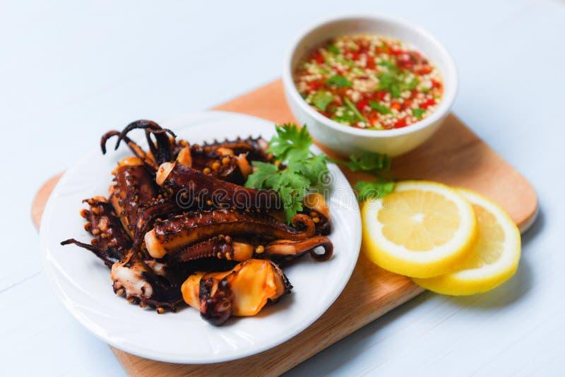 章鱼沙拉用柠檬草本和香料在白色板材-触手乌贼烤了开胃菜食物热和辣辣味番茄酱 库存图片