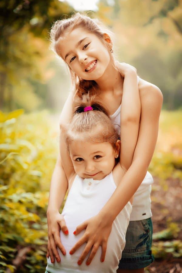 童年、家庭、友谊和人概念-拥抱两个愉快的孩子的姐妹户外 免版税库存照片