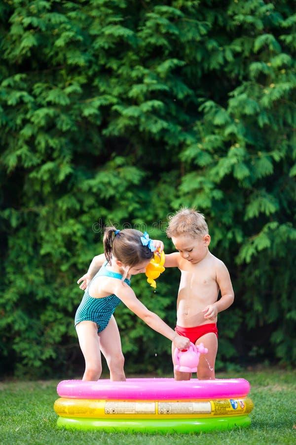 童年与水池的夏天比赛 白种人兄弟和姐妹戏剧用飞溅塑料玩具喷壶倾吐的水, 免版税图库摄影