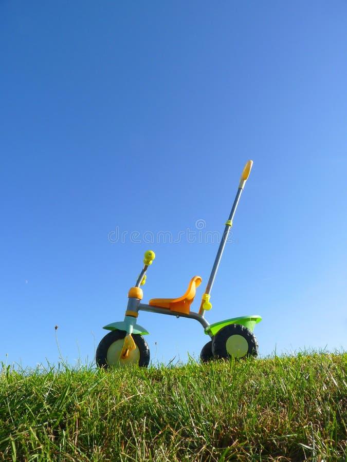 童年在绿草和蓝天背景的玩具三轮车 免版税库存图片