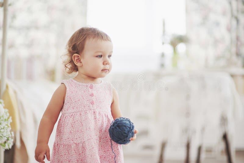 童年概念 逗人喜爱的礼服戏剧的女婴与色的螺纹 白色葡萄酒childroom 免版税库存照片