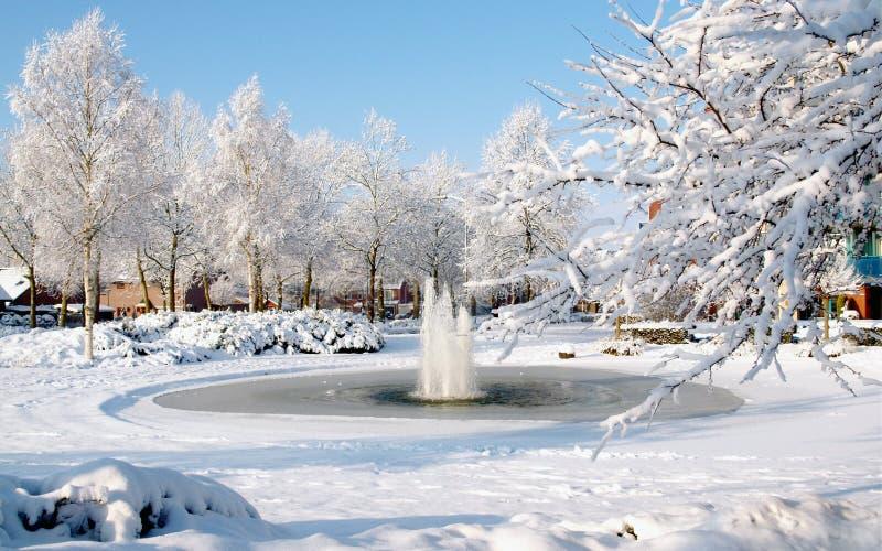 童话冬天风景在Nunspeet,荷兰,有有喷泉的冻池塘的 免版税库存照片