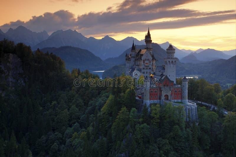 童话新天鹅堡城堡的美好的晚上视图,与在日落期间的秋天颜色,巴法力亚阿尔卑斯,巴伐利亚,德国 免版税图库摄影