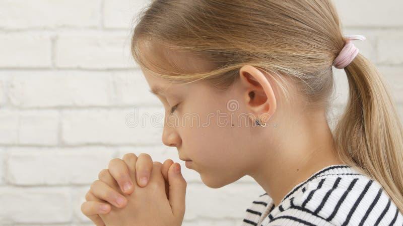 童颜祈祷在吃前的,思考的孩子在厨房,女孩画象里 图库摄影