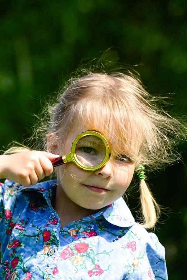 童颜通过放大器 看通过放大镜的美丽的女孩 免版税库存照片