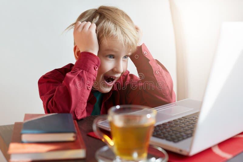 童年、现代技术、互联网和教育概念 疲倦神色的情感可爱的白肤金发的男性,学习在膝上型计算机, 库存照片