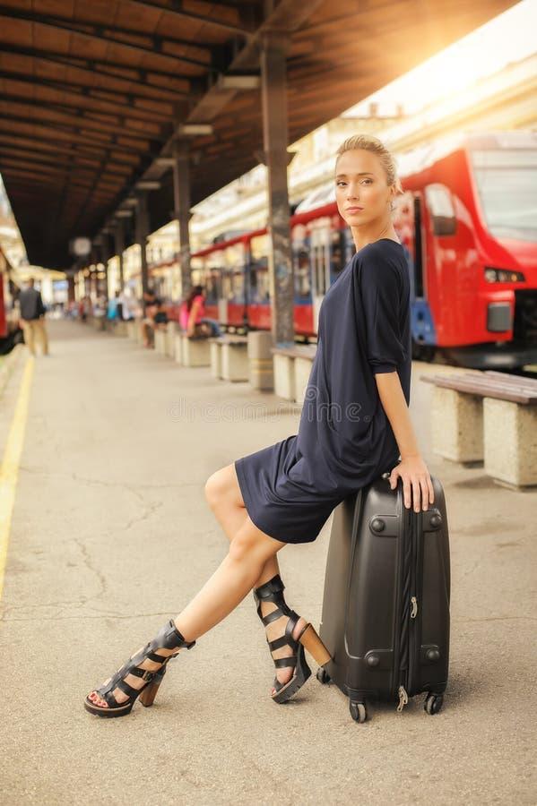 端庄的妇女坐在火车站的手提箱 免版税图库摄影