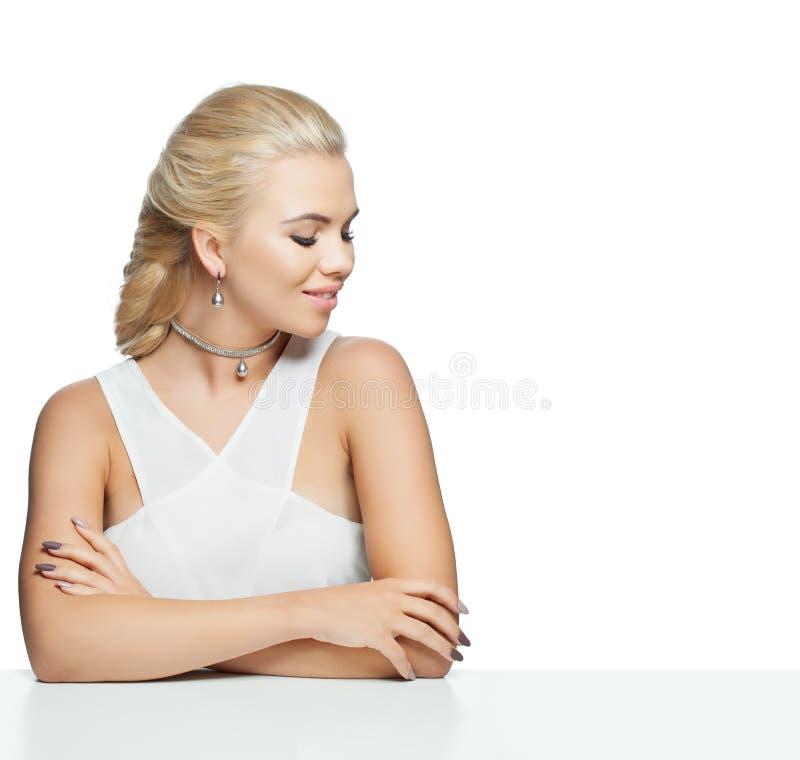 端庄的妇女坐白色桌 在白色背景隔绝的完善的式样女孩 库存照片