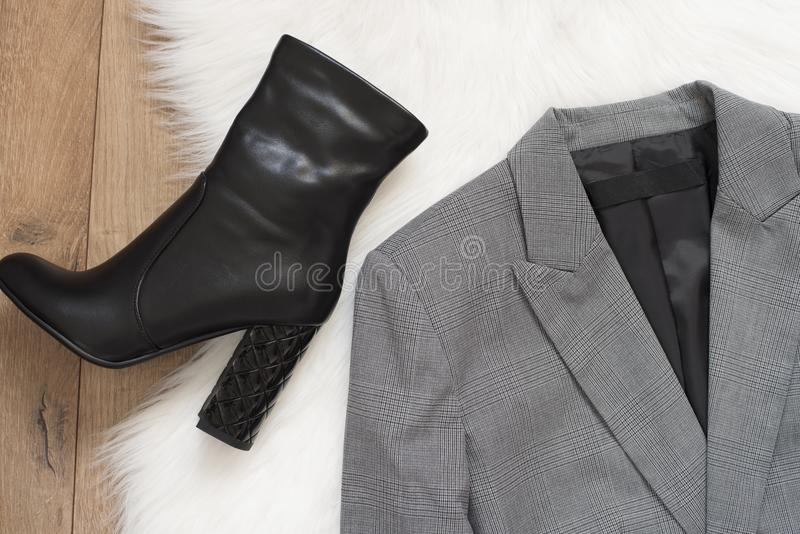 端庄的妇女夹克和黑高跟鞋起动 方格在木背景的一件灰色夹克 时尚和设计, sho的概念 免版税库存图片