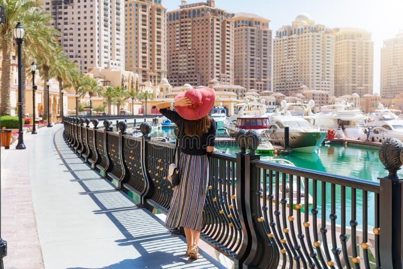 端庄的妇女看小游艇船坞走道在波尔图阿拉伯半岛珍珠在多哈 免版税库存照片