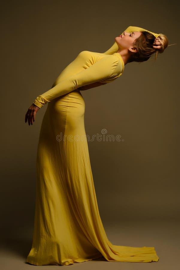 端庄的妇女秀丽黄色长的时尚礼服 库存照片