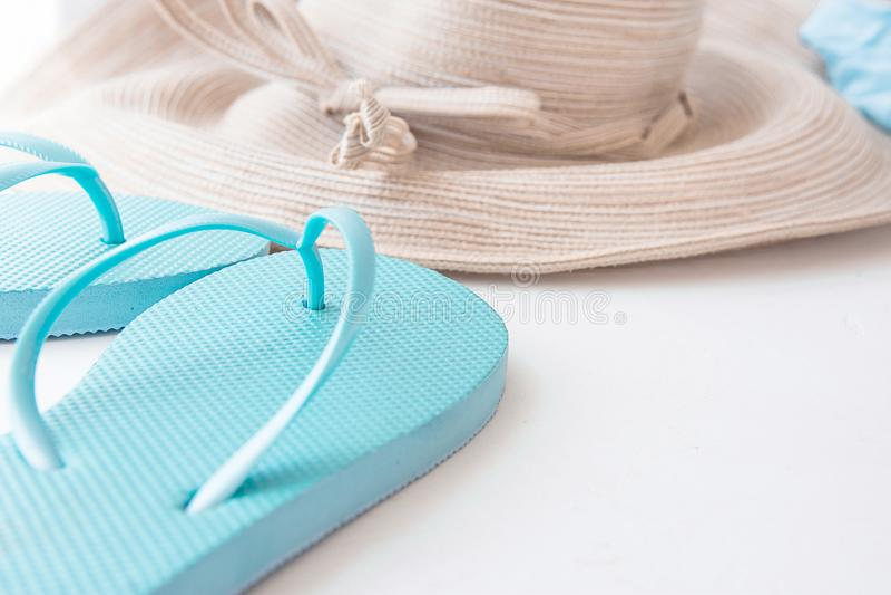 端庄的妇女秸杆有弓蓝色海滩触发器的太阳帽子白色背景海边假期 库存照片