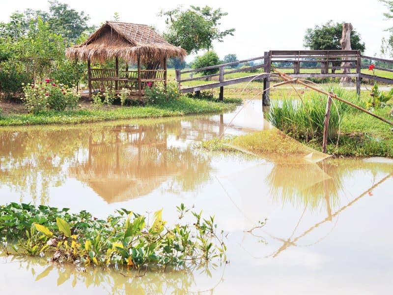 竹小屋和木桥有鱼陷井的在河 库存照片