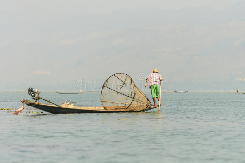 竹小船传染性的鱼的未认出的缅甸渔夫用与手工制造网的传统方式 免版税库存照片