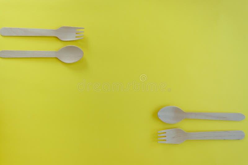 竹木匙子和叉子在黄色背景与空间文本的 Eco友好的厨房用具 免版税库存图片