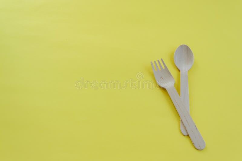 竹木匙子和叉子在黄色背景与空间文本的 Eco友好的厨房用具 免版税库存照片