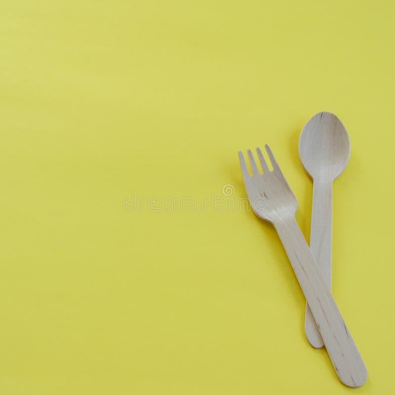 竹木匙子和叉子在黄色背景与空间文本的 Eco友好的厨房用具 库存图片