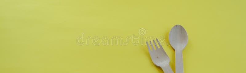 竹木匙子和叉子在黄色背景与空间文本的 Eco友好的厨房用具 图库摄影