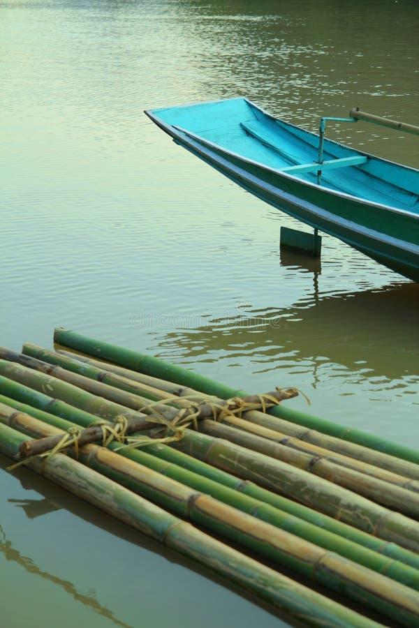 竹木筏和蓝色小船在水 图库摄影