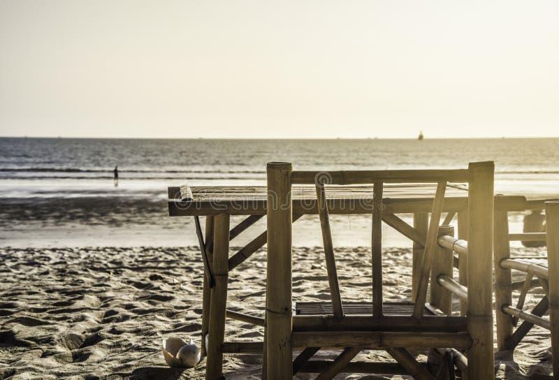 竹桌和椅子由海位子的能看看法 免版税库存照片