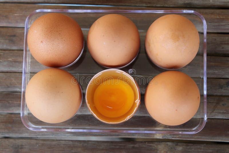 竹桌塑料盒中六个棕色鸡蛋的特写,一个破蛋,顶视图 免版税图库摄影