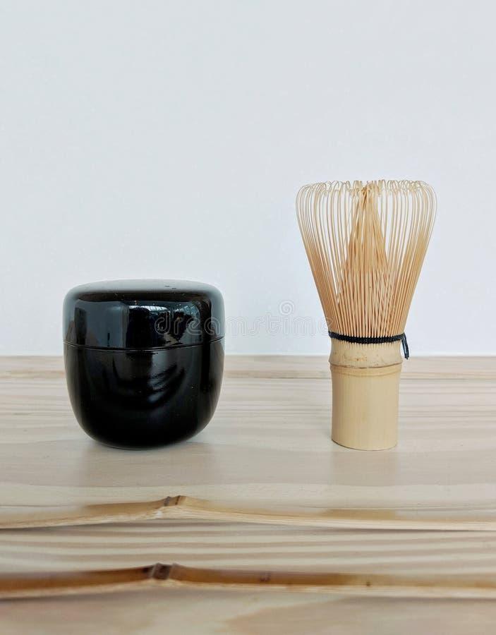 竹茶扫和一个黑发光的小matcha茶罐 免版税库存照片