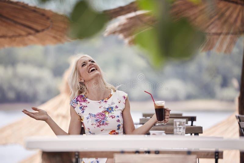 笑一个的少妇, 25岁,查寻上面,坐在海滩咖啡馆,从杯子的饮用的咖啡 免版税库存照片