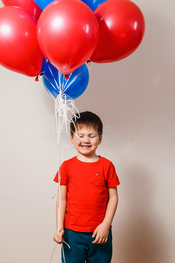 笑一件红色的衬衣的男孩拿着氦气气球和,眼睛关闭了.