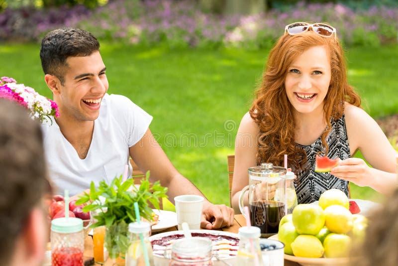 笑与他们的朋友d的一对多文化夫妇的特写镜头 免版税库存照片