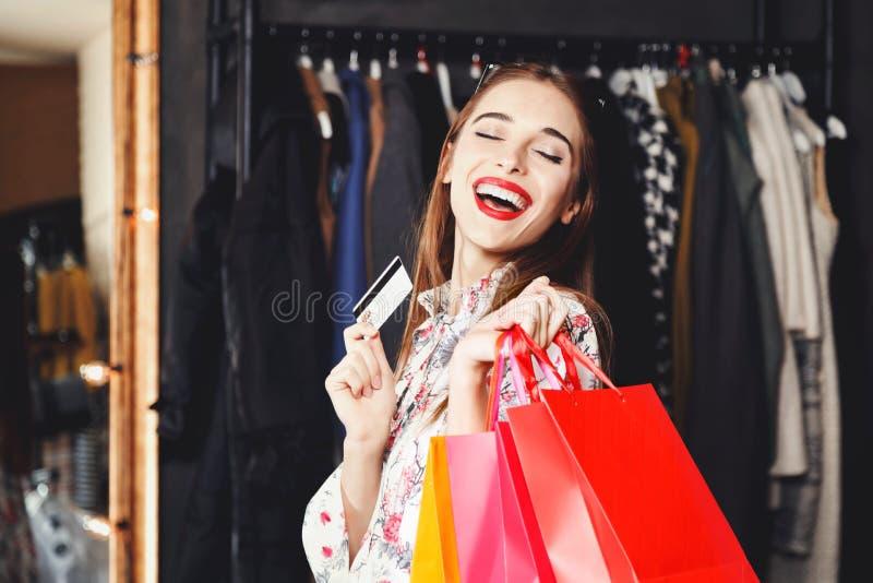 笑与信用卡和购物袋的俏丽的妇女 库存照片