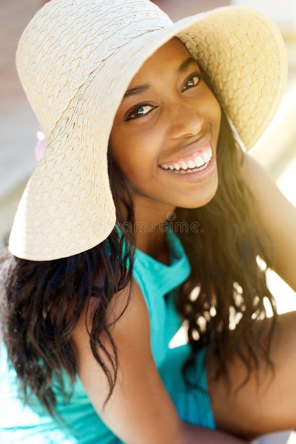 笑与太阳帽子的年轻非裔美国人的妇女 图库摄影