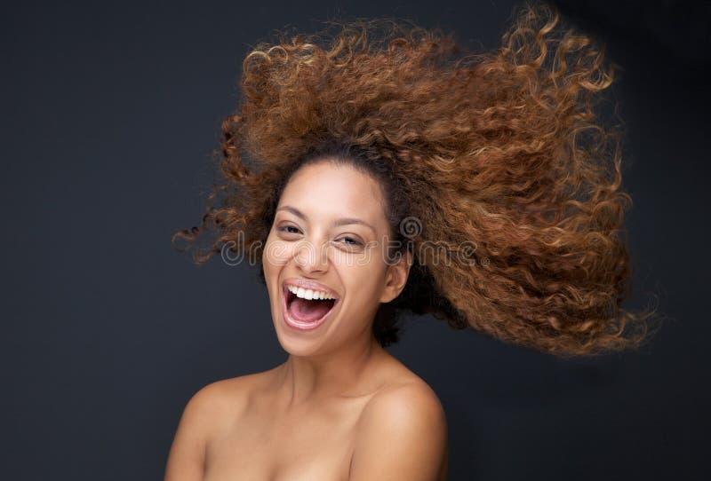 笑与头发吹的一个可爱的少妇的画象 免版税库存图片