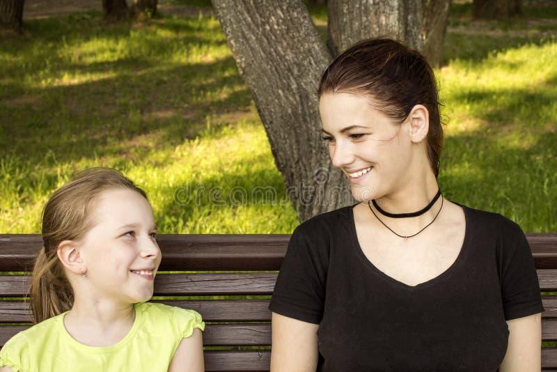 笑两个的女孩坐长凳谈话和 免版税库存图片