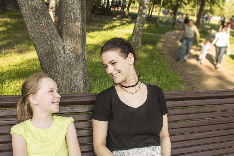 笑两个的女孩坐长凳谈话和 免版税图库摄影
