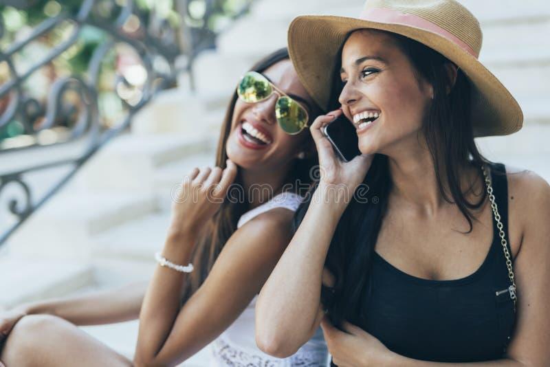 笑两个美丽的女孩,当谈话在电话时 库存照片