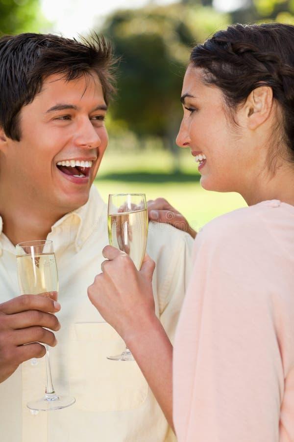 笑二个的朋友,当拿着杯香槟时 库存照片