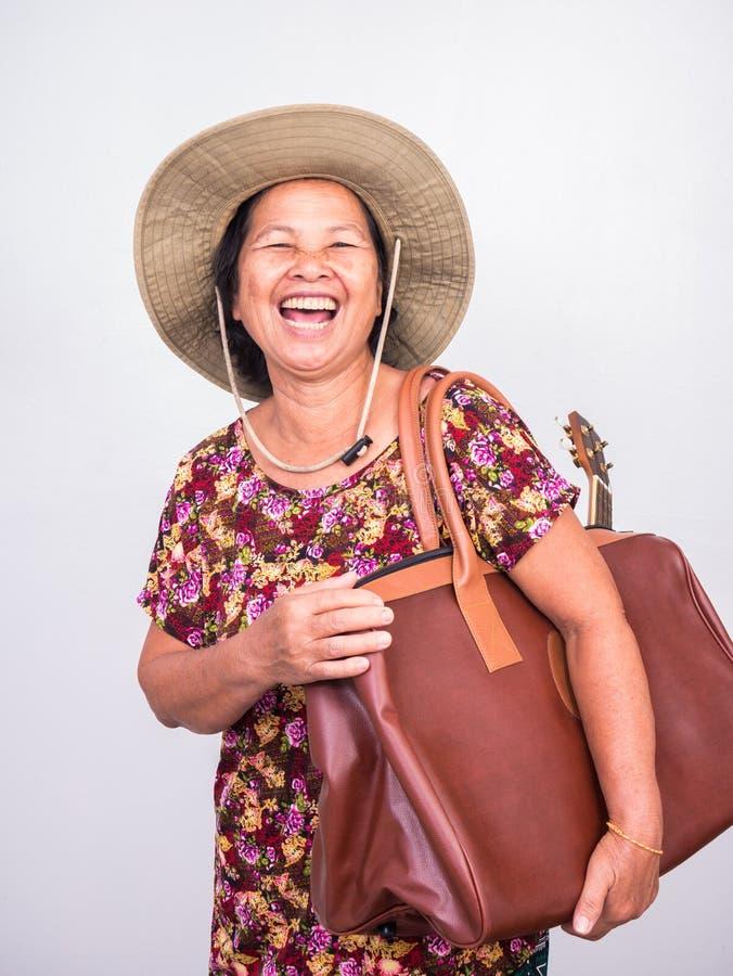 笑亚裔senoir的妇女,当运载尤克里里琴和大褐色时 库存图片