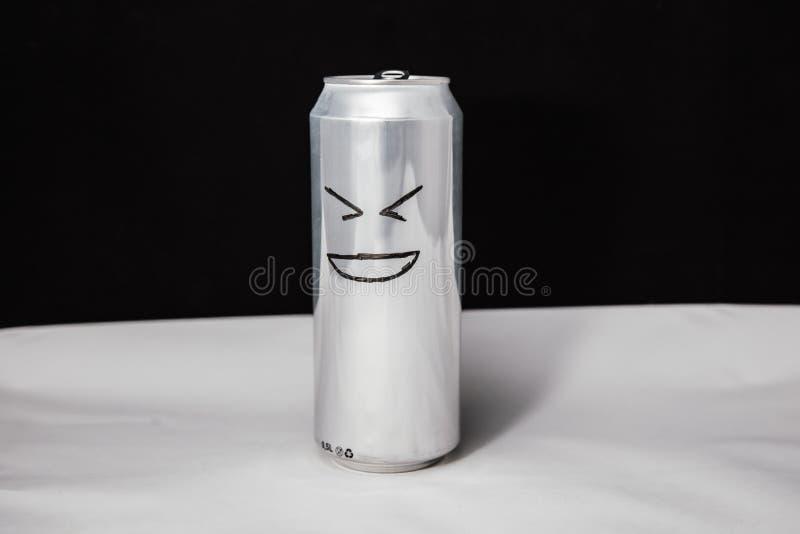 笑人的概念 咧嘴在铝罐的意思号,与XD面孔的Emoji 在黑色背景 免版税库存图片