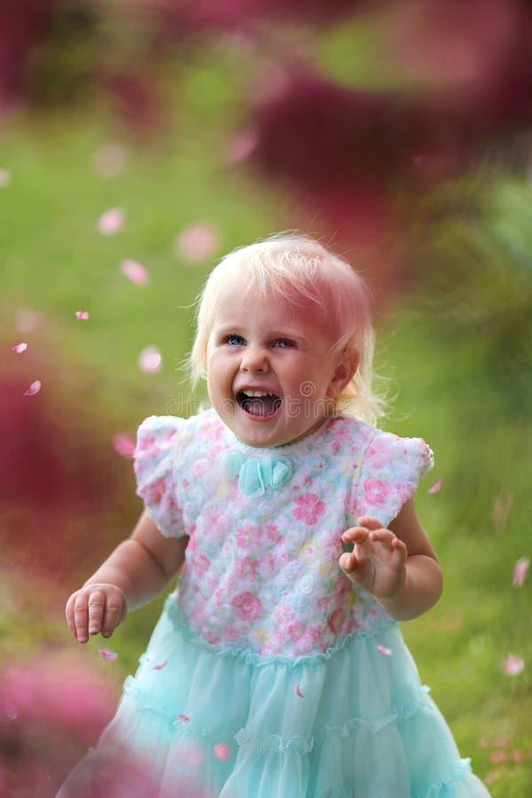 笑作为花哥斯达黎加的花瓣飘落的愉快的年轻小孩女孩 免版税库存照片