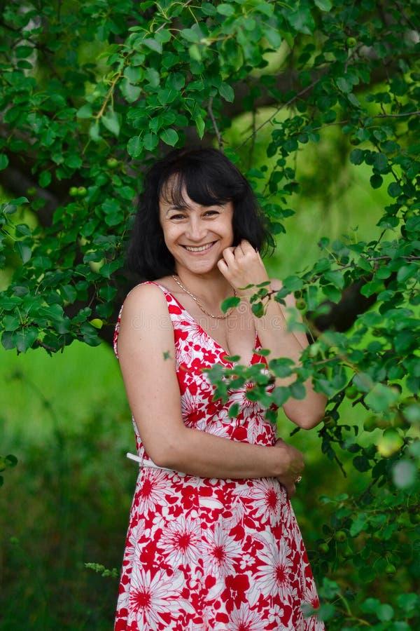 笑反对绿色树背景的愉快的女孩 喜悦的概念 愉快的微笑的妇女 愉快的快乐的微笑的深色的妇女wi 免版税图库摄影