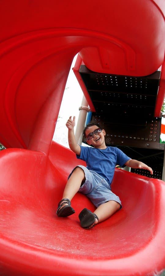 笑和下滑下来在一张螺旋幻灯片的男孩 图库摄影