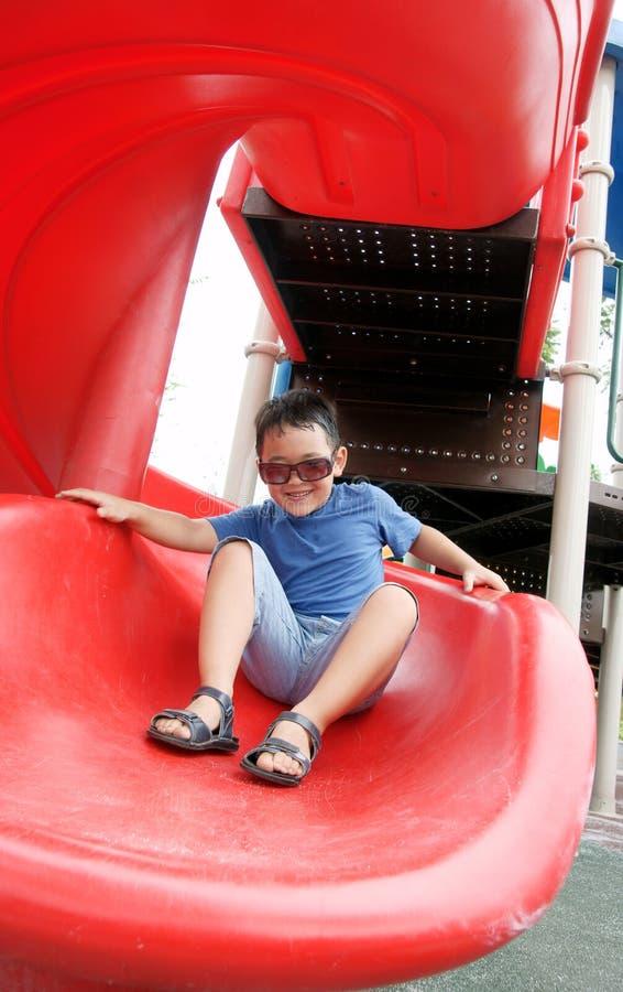 笑和下滑下来在一张螺旋幻灯片的男孩 免版税库存照片