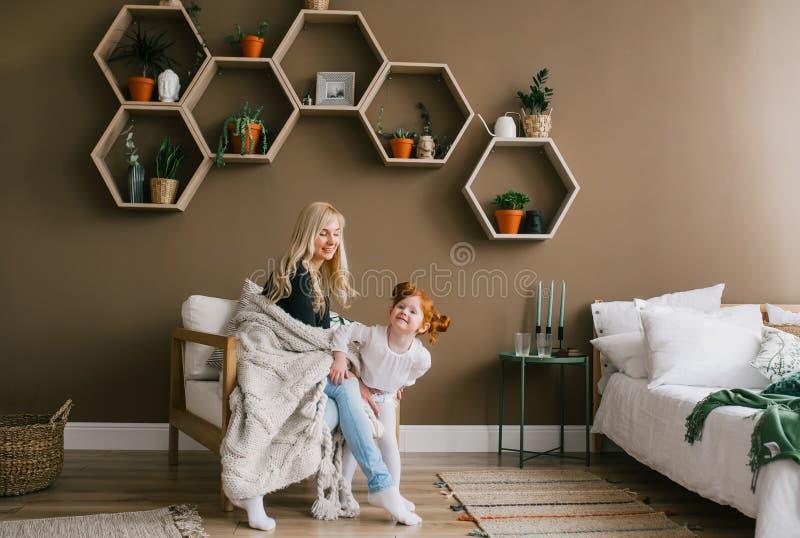 笑和使用与一点女儿的愉快的年轻白肤金发的母亲在家庭卧室 免版税图库摄影