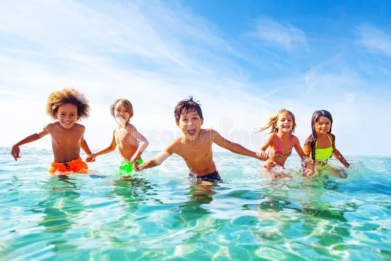 笑和使用在水中的孩子在海边 免版税库存图片