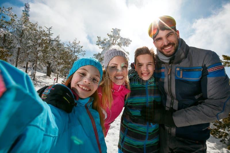 笑和做selfie的家庭冬天滑雪假期 免版税库存图片