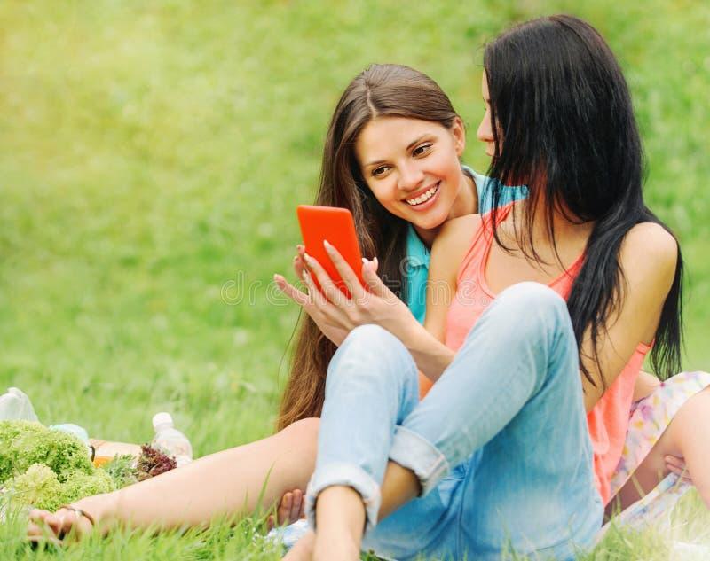 笑和分享在一个巧妙的电话的两个妇女朋友图片 免版税库存图片